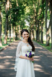Beautiful young smiling brunette bride in wedd dress with bouquet of flowers in hands outdoors on the background of green leaves Stock Image