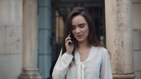 Beautiful Young Smiling Brunette Student Girl Talking on her Smartphone, Walking Outdoors at Old Architecture on stock video footage