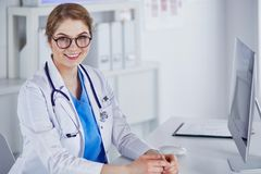 Beautiful young smiling female doctor sitting at the desk stock photography