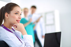 Beautiful young smiling female doctor sitting at Stock Image