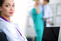 Beautiful young smiling female doctor sitting at Stock Photo