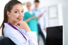 Beautiful young smiling female doctor sitting at Stock Photography