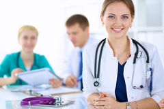 Beautiful young smiling female doctor sitting at Royalty Free Stock Image