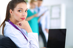 Beautiful young smiling female doctor sitting at Royalty Free Stock Images