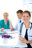 Beautiful young smiling female doctor sitting at Royalty Free Stock Photography