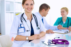 Beautiful young smiling female doctor sitting at Royalty Free Stock Photo
