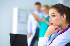 Beautiful young smiling female doctor sitting at Royalty Free Stock Photos
