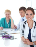 Beautiful young smiling female doctor sitting at Stock Photos