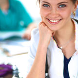 Beautiful young smiling female doctor sitting at the desk Royalty Free Stock Image