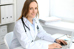 Beautiful young smiling female doctor sitting at the table near window in hospital Royalty Free Stock Image