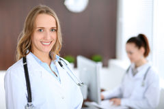 Beautiful young smiling female doctor standing in a hospital with her colleague in the background Stock Photo