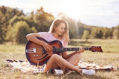 Beautiful young smiling female plays acoustic guitar, sits cross legs on green grass, being in good mood, learns new song, has app. Ealing appearance. People royalty free stock photo