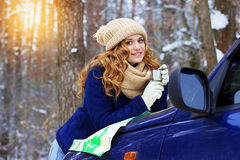 Beautiful young smiling girl drinking tea on the map on car bonnet, wearing blue jacket. Travel girl. Stock Photography