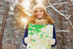 Beautiful young smiling girl holding a map in the forest, wearing blue jacket. Travel girl. Royalty Free Stock Photo