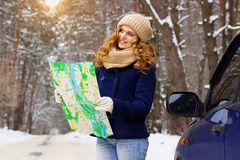 Beautiful young smiling girl holding a map and standing on the road near a car, wearing blue jacket. Travel girl. Stock Image