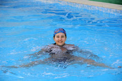 Beautiful young smiling girl sailling in pool in kerchief. Beautiful young smiling girl sailling in pool in blue kerchief Royalty Free Stock Photo