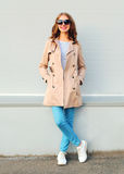 Beautiful young smiling girl wearing a beige coat and black sunglasses standing over grey. Background Stock Images