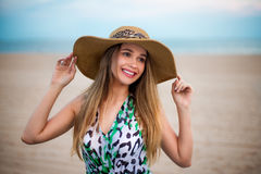 Beautiful young smiling girl wearing a hat on the beach. Happy girl enjoying the summer time on sand beach near the ocean and hold Royalty Free Stock Photography
