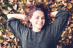 Beautiful young smiling girl woman with wavy hair lies on fallen royalty free stock image