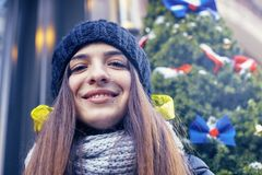 Beautiful young woman in winter. Beautiful young smiling woman against a wall decorated with a Christmas wreath Royalty Free Stock Image
