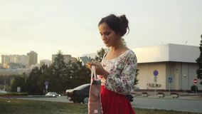 Beautiful young smiling woman in cute dress with shopping colorful bags using smartphone outdoors in slowmotion stock video