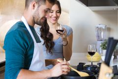 Beautiful young smiling woman drinking red wine while her husband preparing lunch in the kitchen at home royalty free stock photography