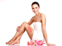 Beautiful young smiling woman with flowers using a scrub. Isolated on white Royalty Free Stock Image
