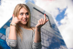 Beautiful young smiling woman gesturing mobile phone near ear Royalty Free Stock Photography