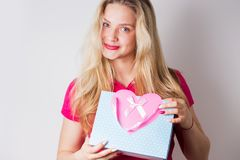 Beautiful young smiling woman holding decorated packages on white background. And looking at the camera, gift for a birthday or Valentine`s day royalty free stock photo