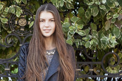 Beautiful young smiling woman with long dark hair. Beautiful woman with long dark hair is wearing grey dress and black jacket. Closeup portrait of young nice Royalty Free Stock Images