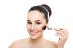 Beautiful young smiling woman with a makeup brush Stock Photos