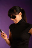 Beautiful young smiling woman with mobilephone. Violet background Royalty Free Stock Images