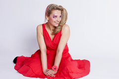 Beautiful young smiling woman in a red dress on a white backgrou Stock Images