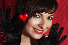 Beautiful young smiling woman with red heart in her hand Stock Image