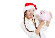 Beautiful, young smiling woman, in santa helper red hat, holding piggy bank, happy excited Royalty Free Stock Photos