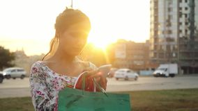 Beautiful young smiling woman with shopping colorful bags using smartphone outdoors during sunset in slowmotion stock video footage