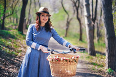 Beautiful young smiling woman with short dark hair and hat standing near bicycle with basket of huge bouquet of chamomiles.Summer Royalty Free Stock Photos
