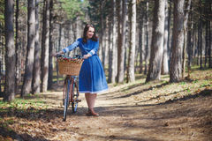 Beautiful young smiling woman with short dark hair and hat standing near bicycle with basket of huge bouquet of Royalty Free Stock Photography