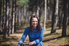 Beautiful young smiling woman with short dark hair and hat standing near bicycle with basket of huge bouquet of Royalty Free Stock Images