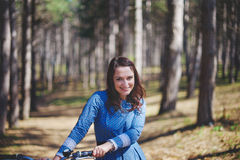 Beautiful young smiling woman with short dark hair and hat standing near bicycle with basket of huge bouquet of Stock Photo
