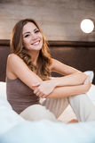 Beautiful young smiling woman sitting on a bed Stock Photography