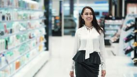 Beautiful young smiling woman walks through sales area in cosmetics shop. Beautiful young woman smiling walks through sales area in cosmetics shop. Concept of stock footage