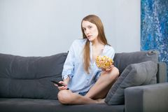 Beautiful young smiling woman watching a movie in the bed and eating popcorn. Stock Photos
