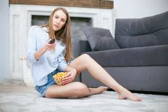 Beautiful young smiling woman watching a movie in the bed and eating popcorn. Royalty Free Stock Images