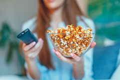 Beautiful young smiling woman watching a movie in the bed and eating popcorn. Royalty Free Stock Photo