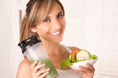 Beautiful young smiling woman wearing a white t-shirt and holding a healthy salad with one hand and therm of juice in. Her other hand Stock Photography