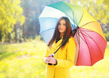 Beautiful young smiling woman wearing a yellow coat with umbrella Stock Photo