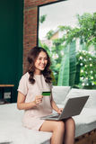Beautiful young smiling woman working on laptop while sitting on Royalty Free Stock Images