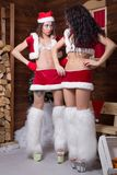 Beautiful young Snow Maiden girls. Two beautiful young Snow Maiden girls in Santa Claus clothes over Christmas background Stock Photos
