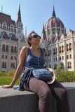 Beautiful young Spanish woman sitting in front of the Parliament of Hungary royalty free stock images